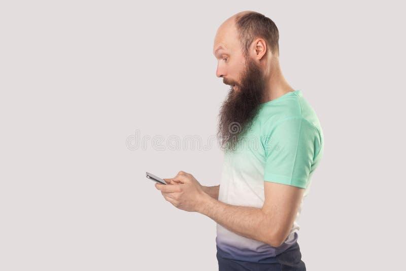 Bocznego widoku portret szokujący łysy brodaty mężczyzna patrzeje mobilnego mądrze telefonu pokazu z zdziwioną twarzą czytelniczy fotografia stock