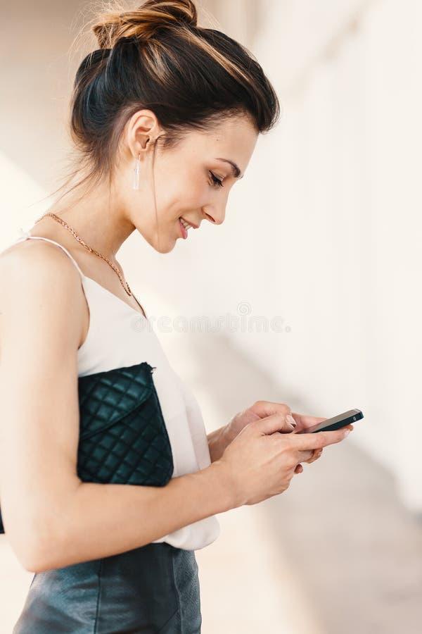 Bocznego widoku portret uśmiechnięta elegancka młoda kobieta używa mądrze telefon fotografia royalty free