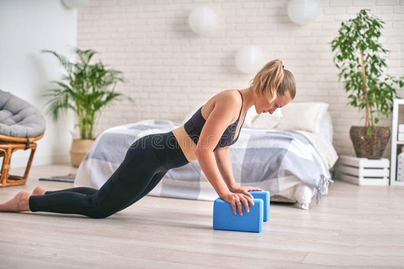 Bocznego widoku profil składna atleta Zostaje w desce i u?ywa joga bloki dla nadgarstk?w obraz stock