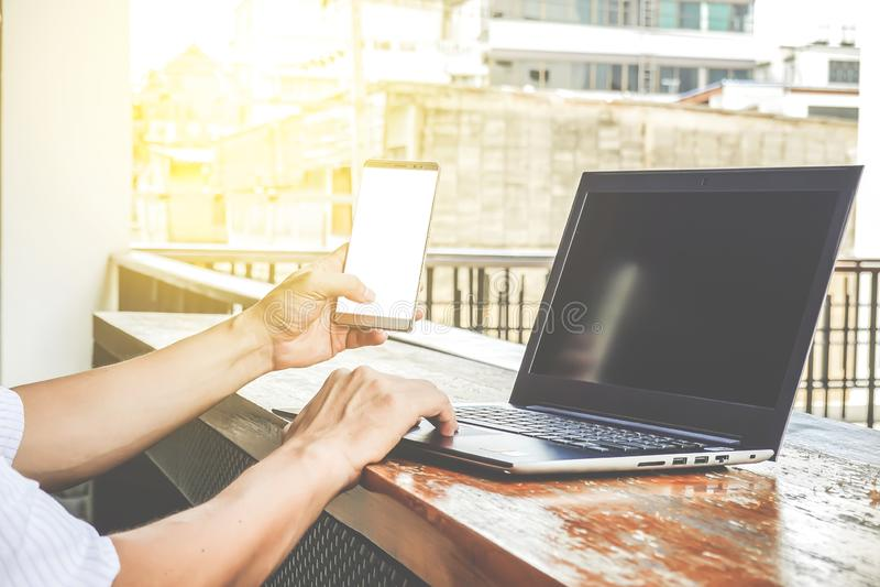 Bocznego widoku strzał pracuje od kawiarni młody biznesmen używać mądrze notebook i telefon obrazy stock