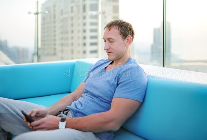 Boczny portret chłodno caucasian facet patrzeje telefon komórkowego outside obraz stock