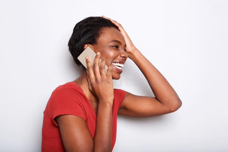 Boczny portret opowiada na telefonie komórkowym i śmiać się szczęśliwa murzynka zdjęcie royalty free