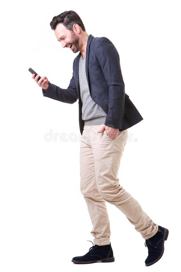 Boczny portret patrzeje telefon komórkowego szczęśliwy mężczyzna zdjęcie royalty free