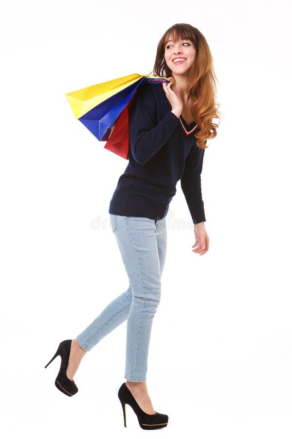 Boczny portret szczęśliwy młodej kobiety odprowadzenie na odosobnionym białym tle z torbami na zakupy obrazy stock