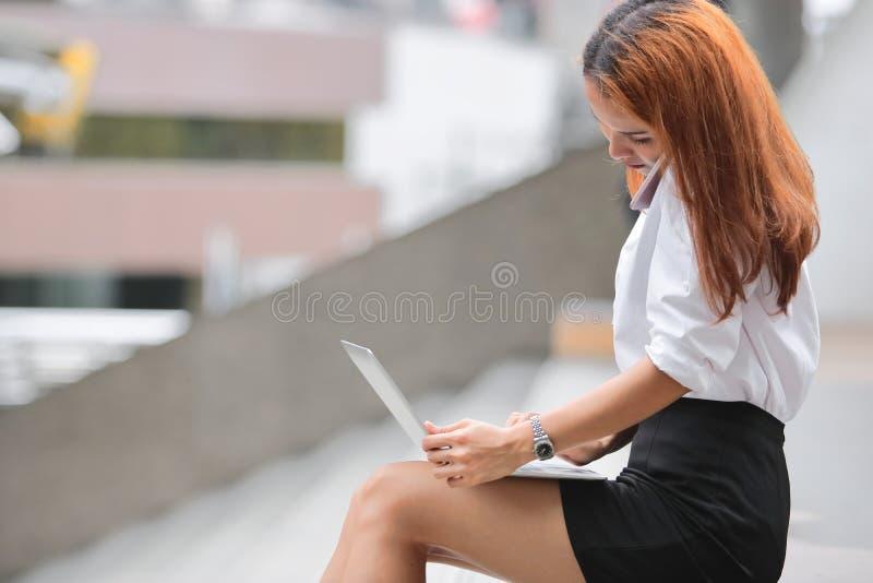 Boczny widok ładna młoda Azjatycka biznesowa kobieta używa laptop i mobilnego mądrze telefon dla pracy przy outside biurem fotografia royalty free