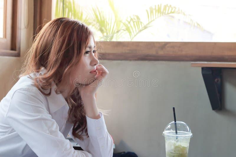 Boczny widok atrakcyjna młoda Azjatycka kobieta z filiżanką przy kawiarnią z kopii przestrzeni tłem zdjęcie stock