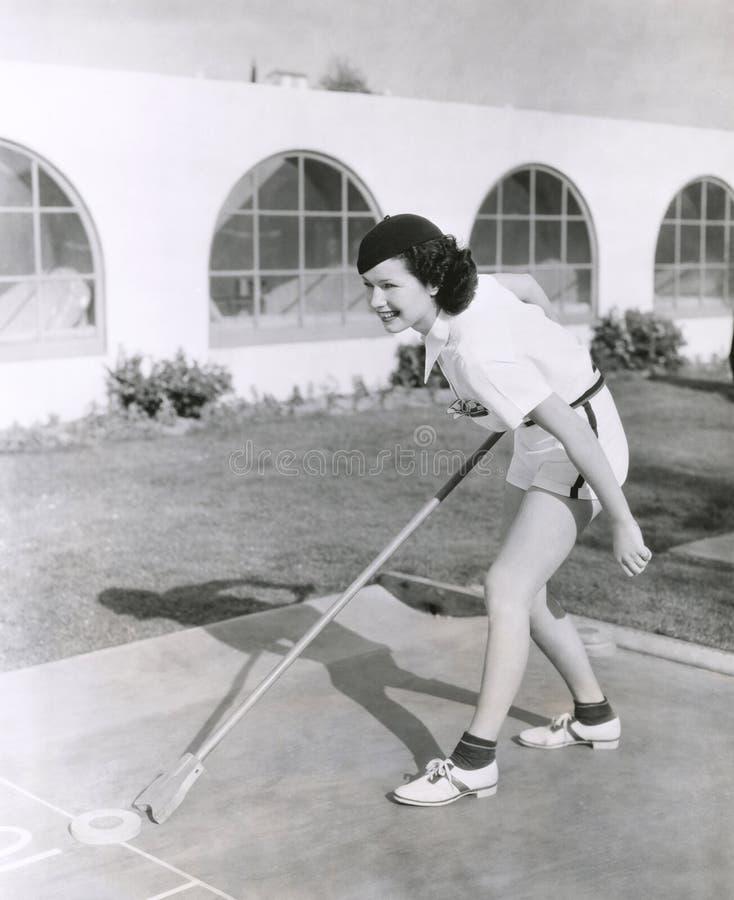 Boczny widok bawić się shuffleboard kobieta zdjęcia stock