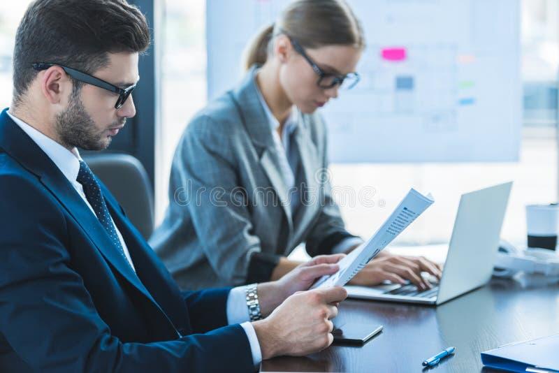 boczny widok biznesmen i bizneswoman patrzeje dokumenty obrazy stock
