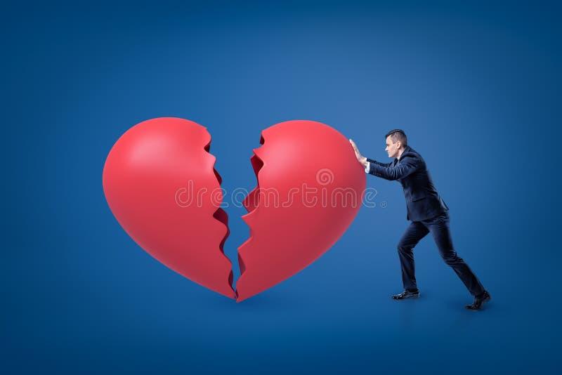 Boczny widok biznesmen opiera naprzód i pcha dużego czerwonego złamane serce zdjęcie royalty free