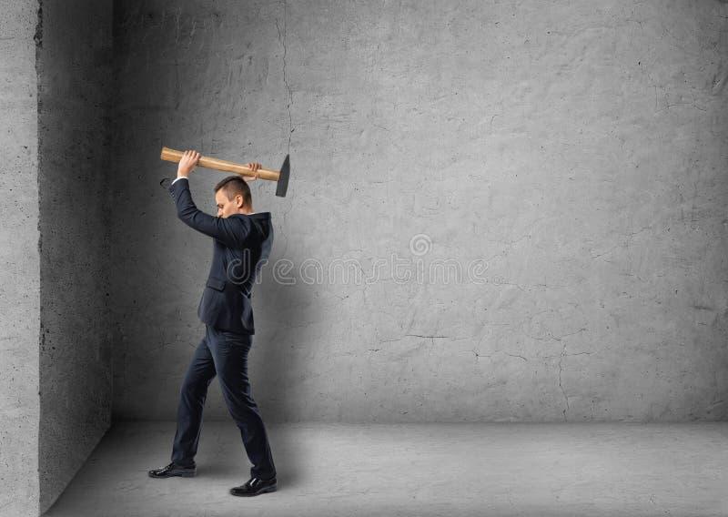 Boczny widok biznesmen rozbija betonową ścianę z młotem zdjęcie stock