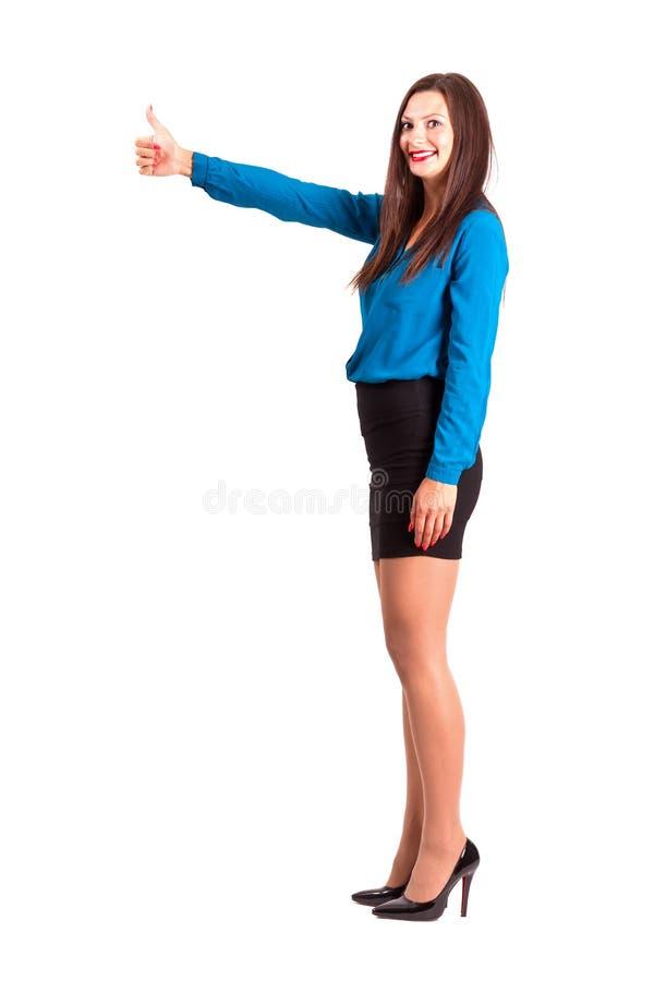 Boczny widok biznesowa kobieta z aprobatami gestykuluje patrzejący kamerę fotografia stock