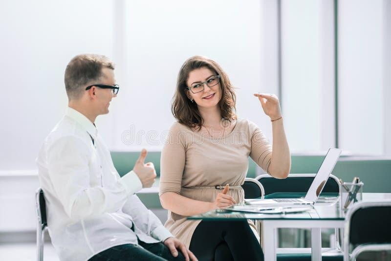 Boczny widok biznesowi koledzy siedzi przy biurkiem dyskutuj? co? obraz royalty free