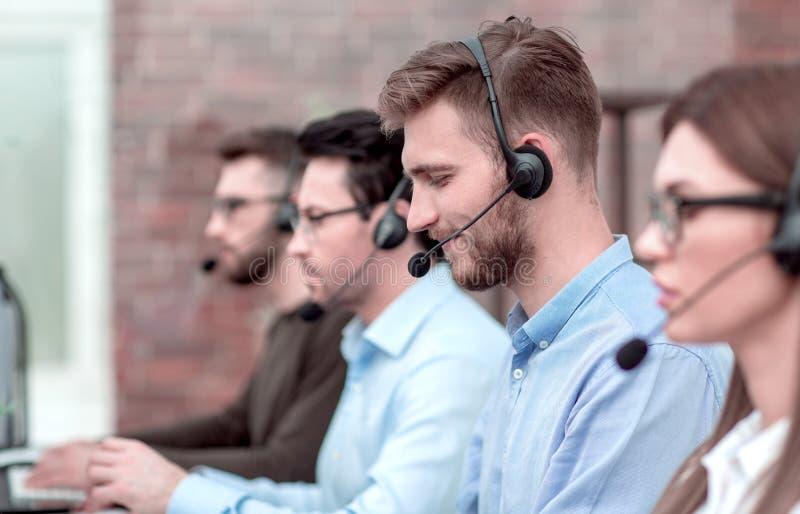 Boczny widok centrum telefoniczne operator i jej koledzy pracujemy w biurze obrazy royalty free