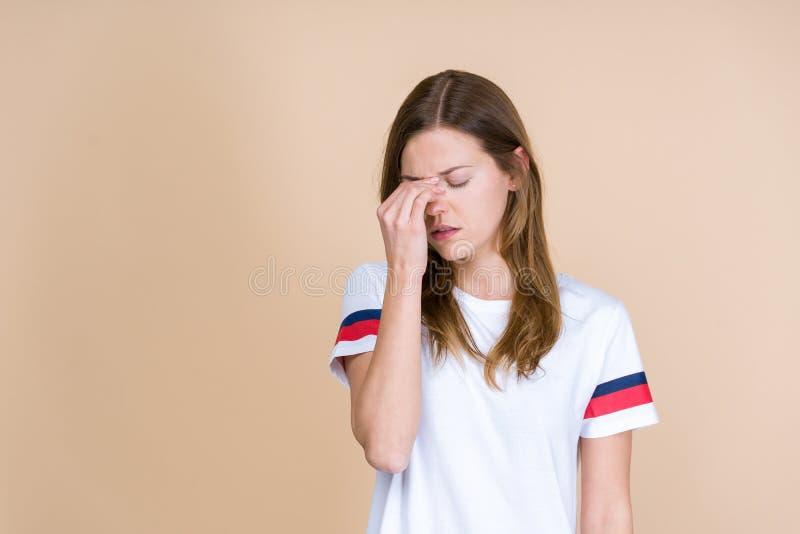 Boczny widok chora młoda dorosła kobieta dotyka nosebrige z zamkniętymi oczami fotografia stock