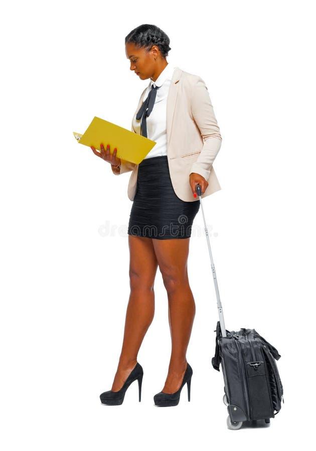 Boczny widok czarny afroamerykanin w formalnym ubiorze z notatnikiem i walizk? zdjęcie royalty free