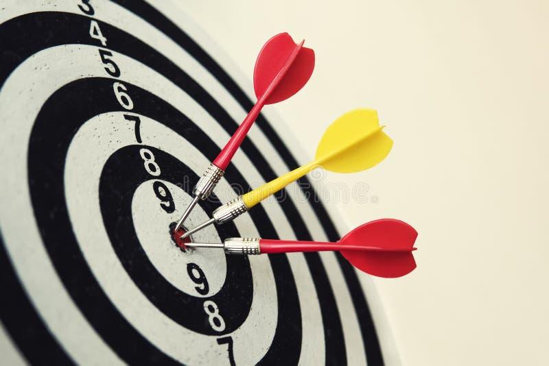 Boczny widok dartboard z trzy strzałkami w bullseye Celujący strzałki miotanie Potrójny bullseye uderzenie Trzy dobrze wykonany obraz stock