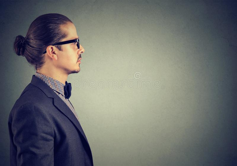 Boczny widok dorosły mężczyzna patrzeje poważny na szarym tle w kostiumu fotografia stock