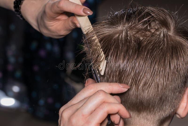 Boczny widok dostaje ostrzyżenie fryzjerem przy śliczna chłopiec zdjęcia stock