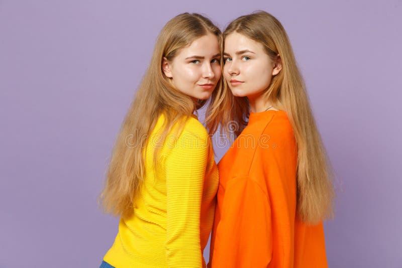 Boczny widok dwa pięknej młodej blondynka bliźniaków siostr dziewczyny patrzeje kamerę na pastelu w żywych kolorowych ubraniach fotografia royalty free