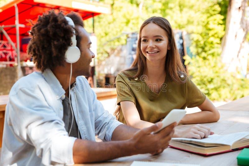 Boczny widok dwa szczęśliwego młodego przyjaciela siedzi stołem obraz royalty free