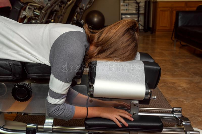 Boczny widok dziewczyna Kłaść na Przechylającym Chiropractic stole fotografia stock