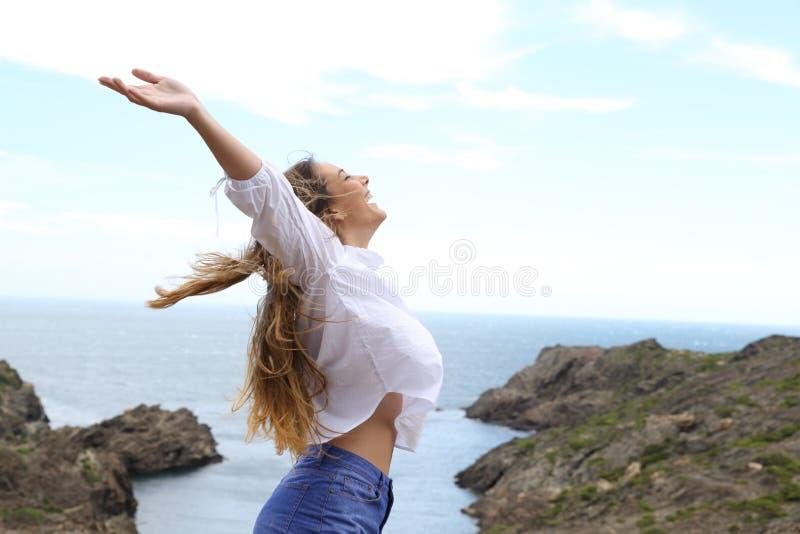 Boczny widok dziewczyny dźwigania radosne ręki wiatr fotografia royalty free