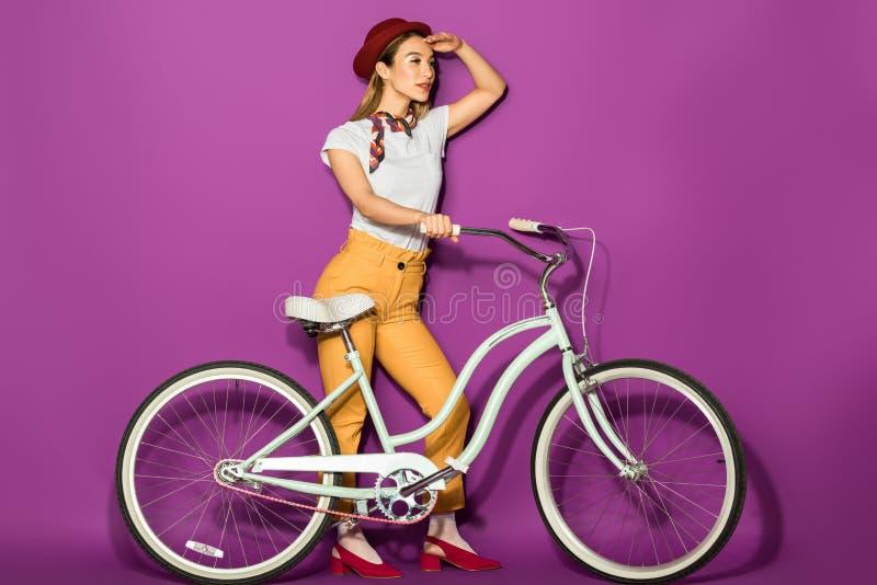 boczny widok elegancka azjatykcia dziewczyny pozycja z rowerem i patrzeć daleko od fotografia royalty free