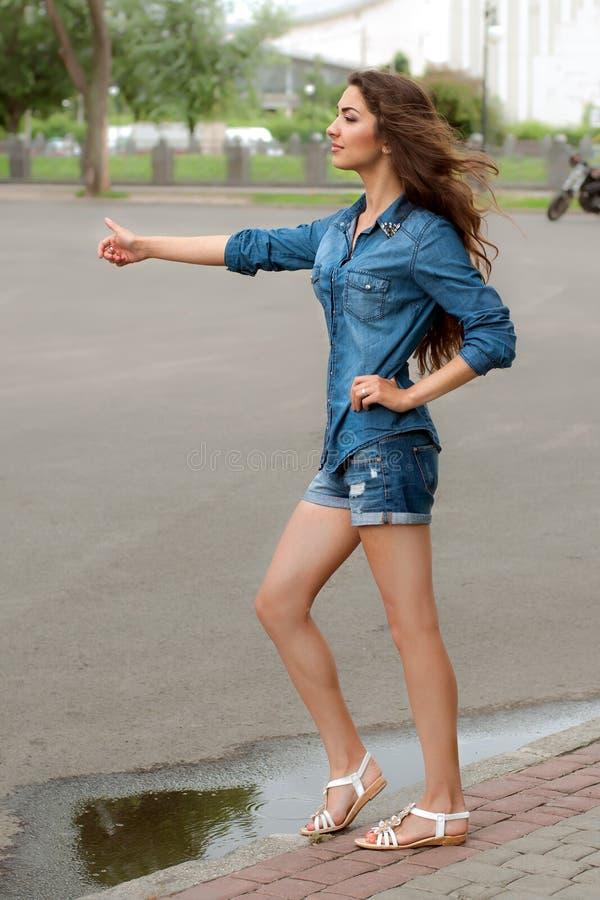 Boczny widok kobieta hitchhiking na miasto drodze fotografia royalty free