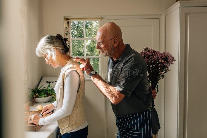 Boczny widok kobieta pracuje w kuchni z jej mężem stoi za bukietem kwiaty z Starszy mężczyzna chuje wiązkę fotografia stock