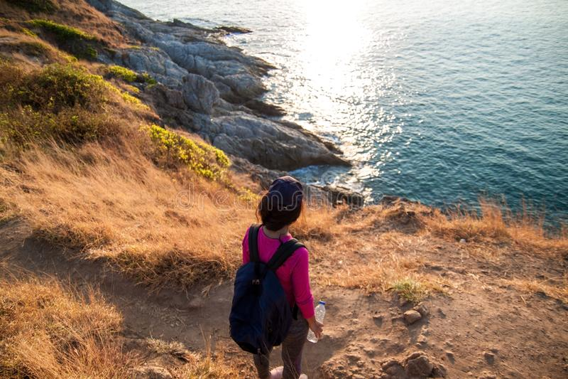 Boczny widok kobieta z plecakiem i smartphone bierze fotografię przy morzem na wzgórzu przeciw niebu zdjęcia stock