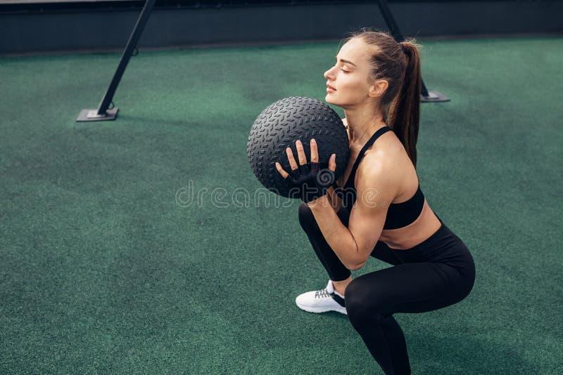 Boczny widok kobiety kucanie z medycyny piłką fotografia royalty free