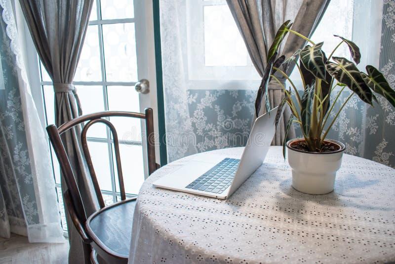 Boczny widok komputer na drewnianym stole obok okno zdjęcie stock