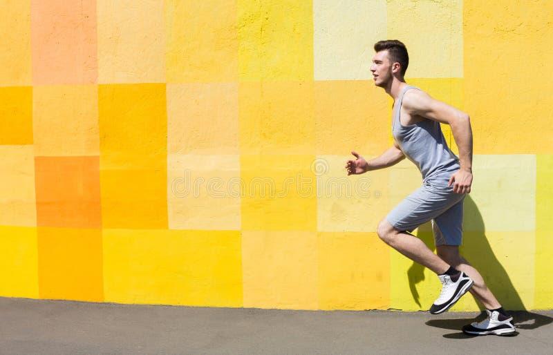 Boczny widok mężczyzna bieg przeciw jaskrawej ścianie obrazy stock