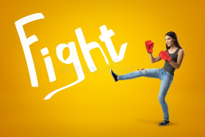 Boczny widok młoda ładna dziewczyna w cajgach, sleeveless wierzchołku i czerwonych bokserskich rękawiczkach z nogą podnoszącą dla obrazy stock