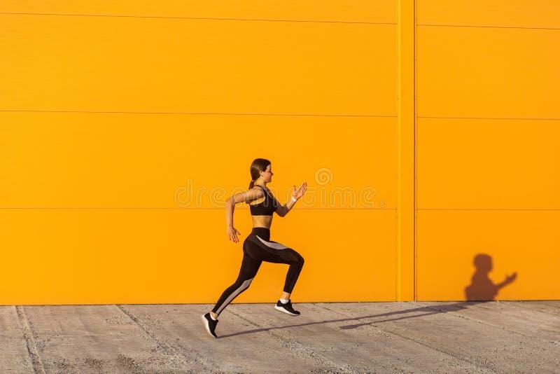 Boczny widok młoda atrakcyjna sporty kobieta jest ubranym czarnego sporwear ćwiczy sport ćwiczy w ranku na ulicie, początek biega zdjęcie royalty free