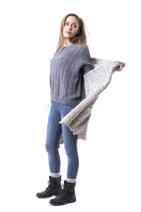 Boczny widok młoda elegancka kobieta w zimie odziewa rozbierać się zdejmujący trykotowego kardigan zdjęcia royalty free