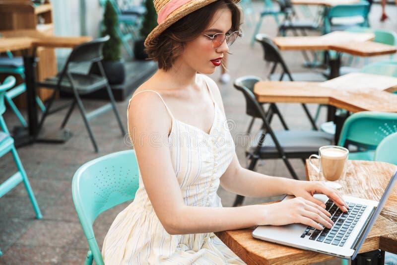 Boczny widok młoda kobieta w smokingowym i słomianym kapeluszu obrazy stock