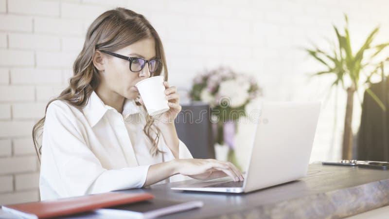 Boczny widok młoda piękna kobieta jest ubranym szkła pisać na maszynie przy jej laptopem w biurze Środka strzał obraz stock