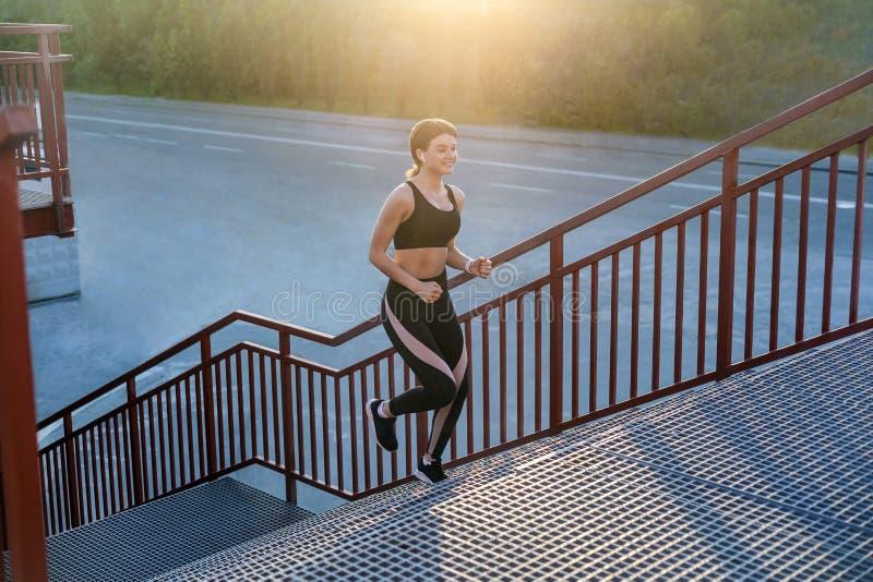 Boczny widok młoda sportowa szczupła piękna kobieta działająca w górę schodków robi cardio interwału szkoleniu w czarnym modnym s obraz stock