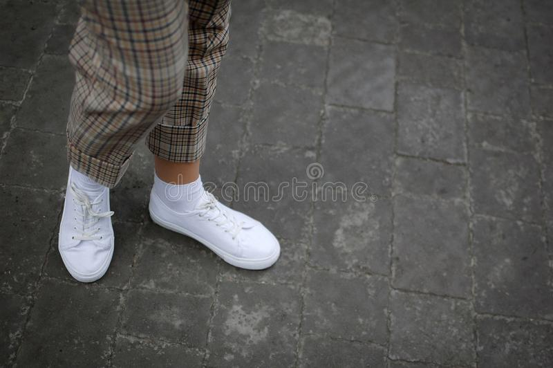 Boczny widok młode kobiety nożne w białych sneakers na asfaltowym tle zdjęcia royalty free