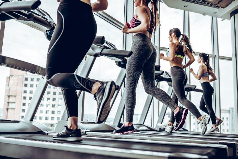 Boczny widok młode piękne kobiety patrzeje oddalony podczas gdy biegający na karuzeli przy gym zdjęcia stock