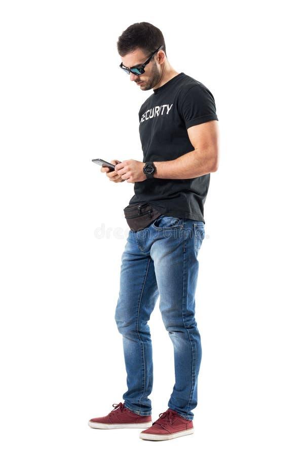 Boczny widok młodego tajnego policjanta pisać na maszynie wiadomość na telefonie komórkowym zdjęcie royalty free