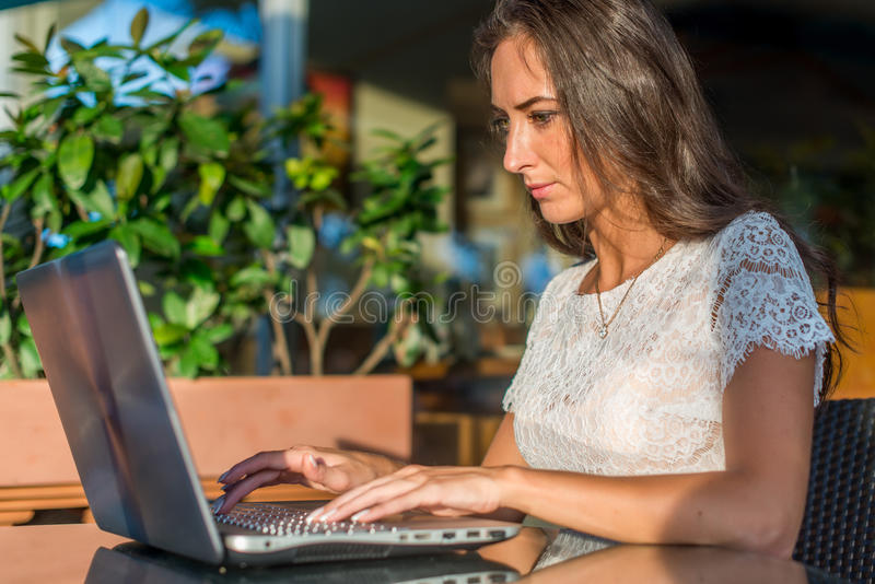 Boczny widok młody żeńskiego pisarza writing na jej laptopie podczas gdy siedzący w parkowej kawiarni Dziewczyny pisać na maszyni obraz stock