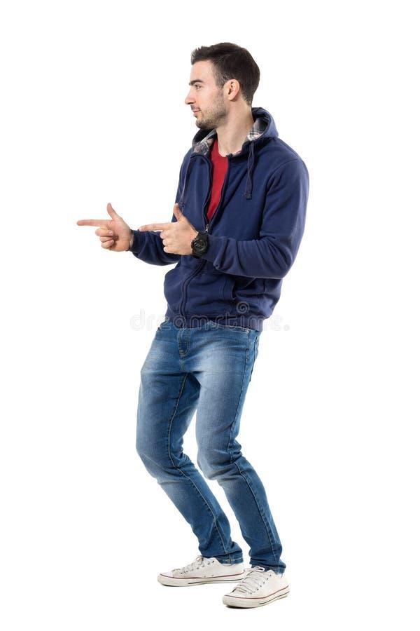 Boczny widok młody przypadkowy facet wskazuje palec pokazuje pistoletowego ręka gest fotografia stock