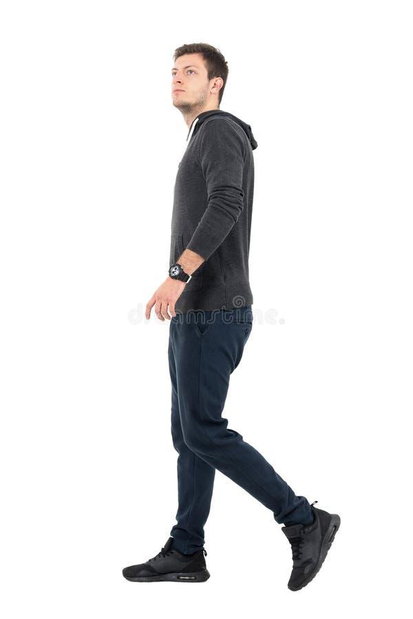 Boczny widok młody przystojny sporty mężczyzna chodzi przyglądający up w bluzy sportowa i potu spodniach fotografia royalty free