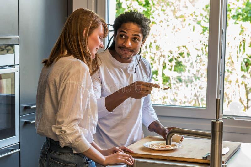 Boczny widok młody wieloetniczny pary kucharstwo, patrzeć each inny i obraz royalty free