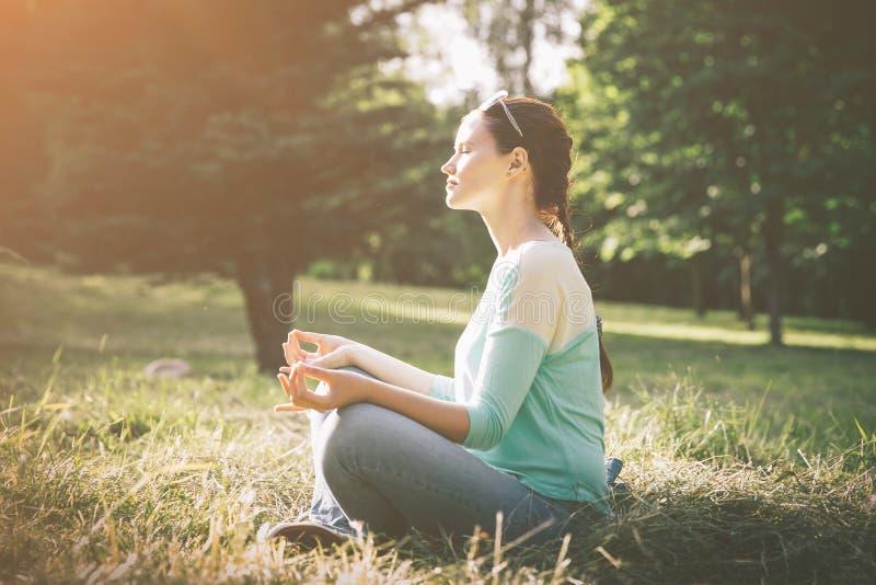 Boczny widok M?oda kobieta medytuje w lotosowej pozyci outdoors fotografia royalty free