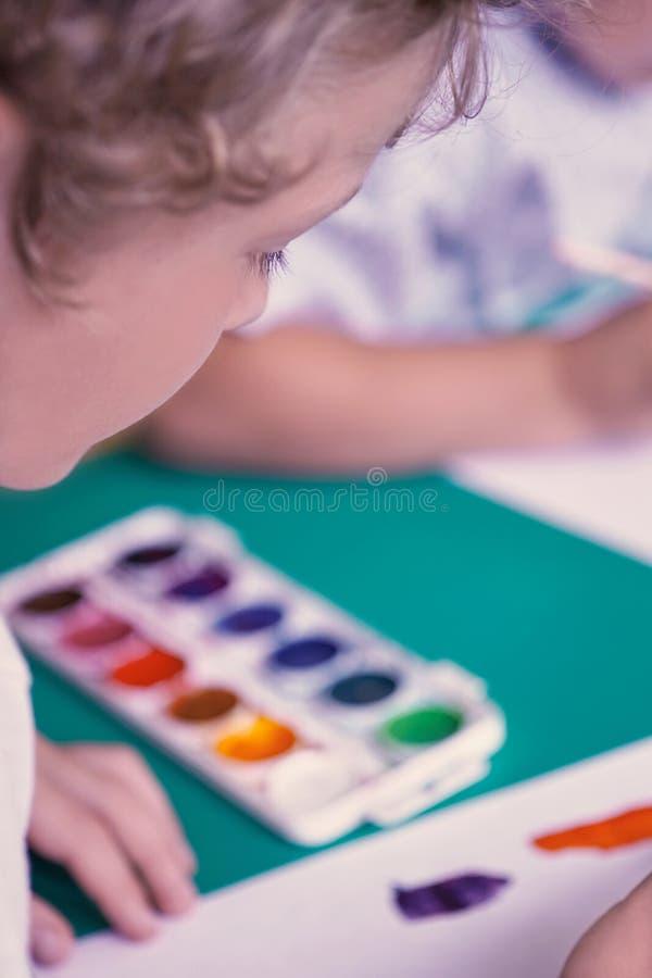 Boczny widok mała kędzierzawa chłopiec patrzeje rysunek Wizerunek z głębią pole obraz royalty free