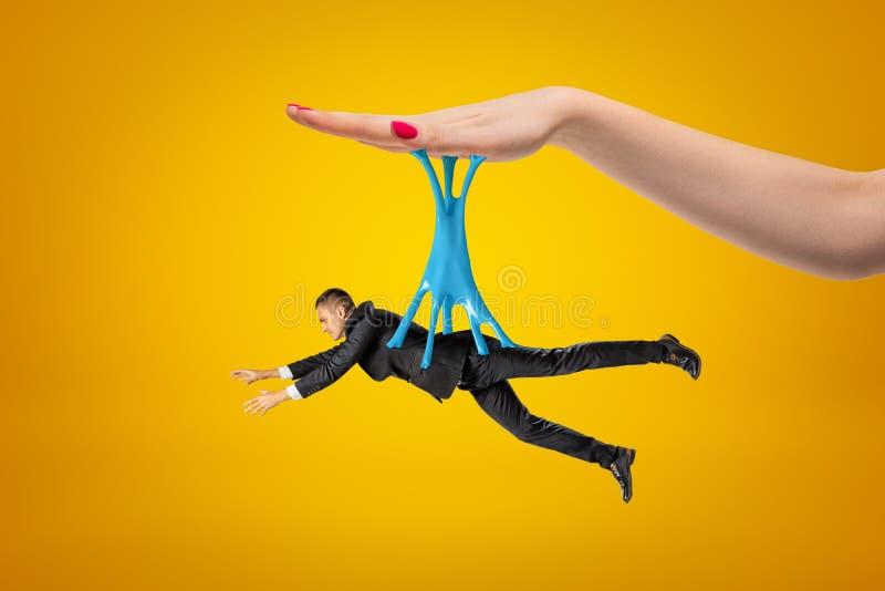 Boczny widok mały mężczyzna w kostiumu obwieszeniu na błękitny kleistym śluzowacieje zablokowanego dużej kobiety ręka na nad żółt obraz stock