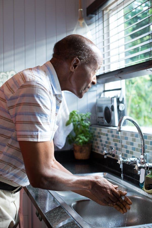 Boczny widok patrzeje oddalony mężczyzna podczas gdy myjący rękę obraz royalty free